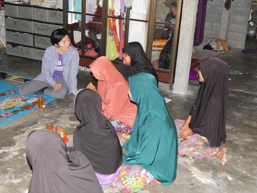 イスラム教徒の村で、女性の住民から話を聞く堀場明子(写真左上)