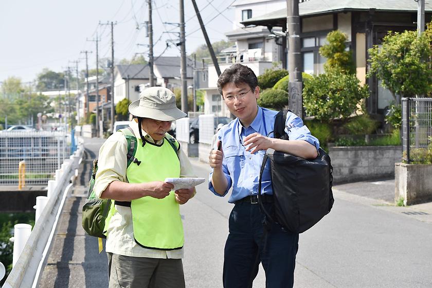 (写真)鎌倉市内の川を調査員とともに歩く塩入研究員