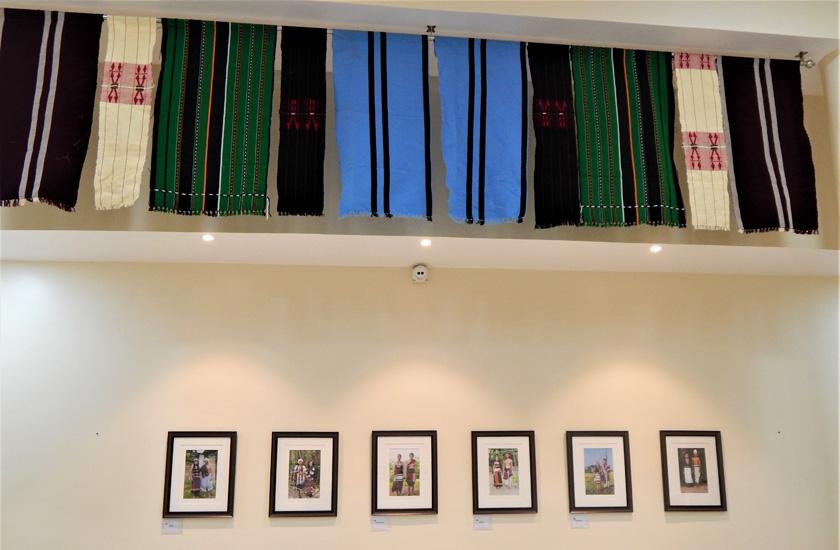 (写真)中央ホールを彩る諸民族の写真と、カラフルな民族衣装の布